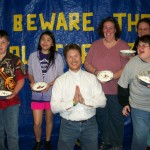 "After the meal, winners of the ""pie-the-pastor' auction line up with their pies.  The Pastor prays for mercy."